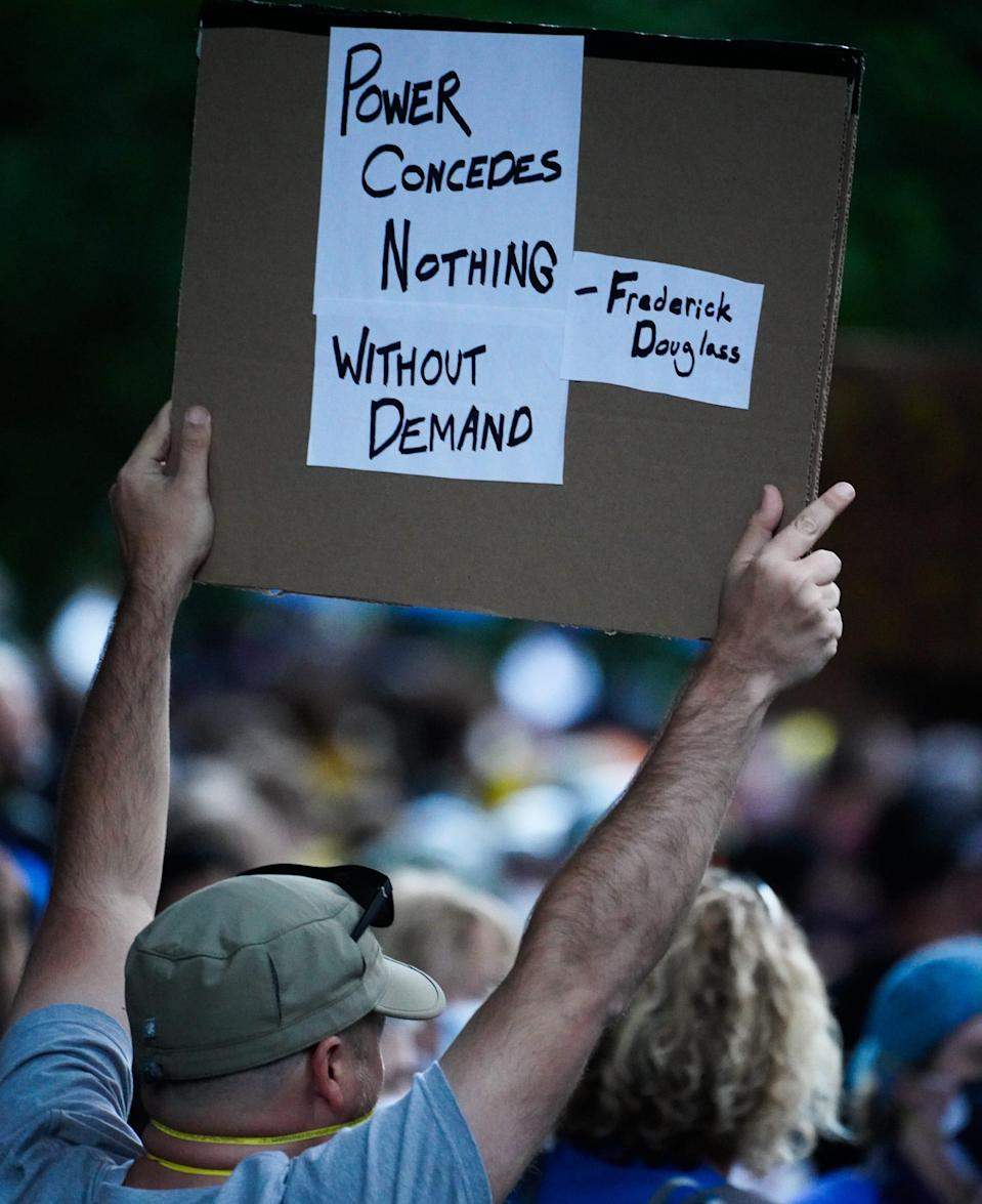 A man participating in a Black Lives Matter protest holds a sign in Portland, Oregon, on July 26, 2020.
