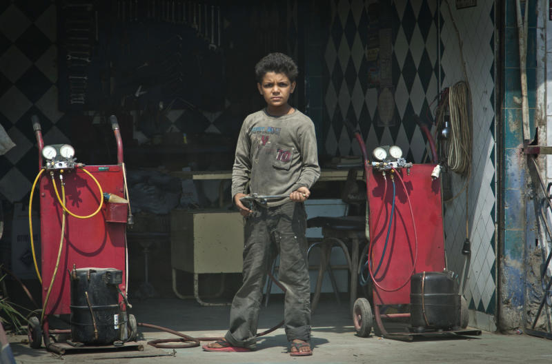 In this Oct. 2, 2012 photo, an Egyptian child stands in front of a tire repair shop where he works in Cairo, Egypt. The Egyptian government estimates that some 1.6 million minors work - almost 10 percent of population aged 17 or under, often in arduous conditions. Other experts put the number at nearly twice that. Some child labor activists worry that protections for children could be loosened further under the new constitution still being written. Earlier this month, the Egyptian Coalition for Children's Rights warned that early drafts of the document did not include as firm prohibitions on child labor as past constitutions.(AP Photo/Khalil Hamra)