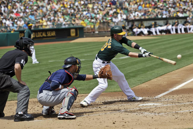 Oakland Athletics' Josh Donaldson, right, drives in a run with a single against the Cleveland Indians during the second inning of a baseball game on Sunday, Aug. 18, 2013, in Oakland, Calif. (AP Photo/Marcio Jose Sanchez)