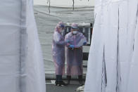 Medical staff wearing protective suits check documents as they wait for people with suspected symptoms of the new coronavirus, at a testing facility in Seoul, South Korea, Wednesday, March 4, 2020. The coronavirus epidemic shifted increasingly westward toward the Middle East, Europe and the United States on Tuesday, with governments taking emergency steps to ease shortages of masks and other supplies for front-line doctors and nurses. (AP Photo/Ahn Young-joon)