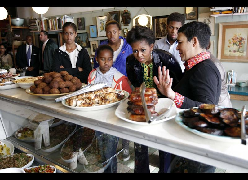 U.S. first lady Michelle Obama (C) stands with Karen Dudley (R), at her restaurant 'The Kitchen' as she makes an unscheduled stop for lunch in Cape Town, South Africa, on June 23, 2011. Founded in 1867 as a mixed community of freed slaves, merchants, and immigrants, the apartheid government in 1965 declared it 'white' and forcibly removed 60,000 residents and bulldozed their homes. US First Lady Michelle Obama kicks off the last leg of her South African tour in Cape Town today, when she will meet with Nobel Peace Prize laureate Desmond Tutu. AFP PHOTO / AP / Charles Dharapak / POOL (Photo credit should read CHARLES DHARAPAK/AFP/Getty Images)