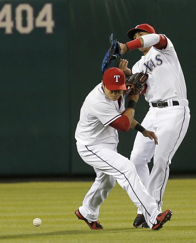 Texas Rangers center fielder Leonys Martin, right, and left fielder Shin-Soo Choo (17) are unable to catch a pop fly hit by Seattle Mariners' Mike Zunino during the fourth inning of a baseball game on Wednesday, April 16, 2014, in Arlington, Texas. (AP Photo/Brandon Wade)