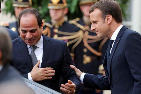 FILE PHOTO: French President Emmanuel Macron greets Egyptian President Abdel Fattah al-Sisi as he leaves  the Elysee palace, in Paris