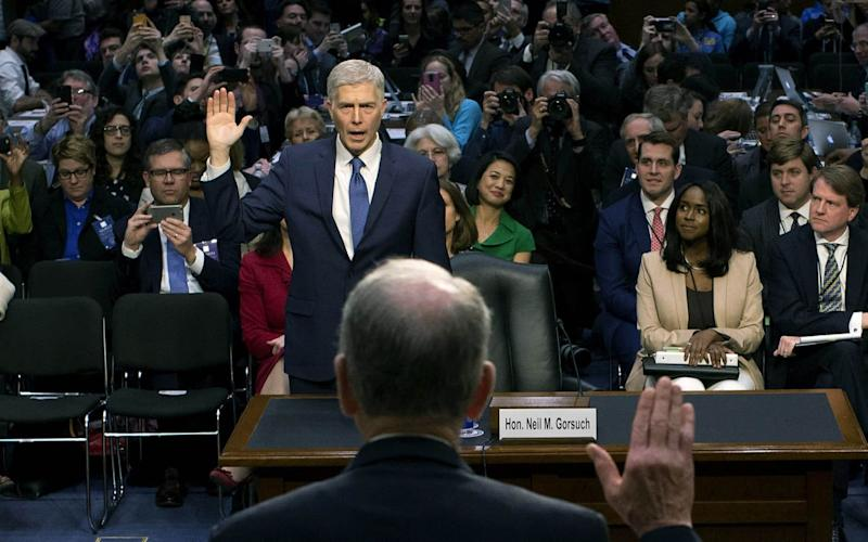 Senate Judiciary Committee Chairman Charles Grassley (R-IA) (back to camera) swears in Judge Neil Gorsuch during the first day of his Supreme Court confirmation hearing - 2017 Getty Images