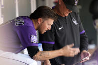 Colorado Rockies starting pitcher Kyle Freeland, left, confers with pitching coach Steve Foster in the dugout in the second inning of a baseball game against the Los Angeles Dodgers, Thursday, Sept. 23, 2021, in Denver. (AP Photo/David Zalubowski)