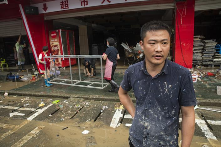 "Yin Jianfeng, outside the supermarket he manages in Shexian, says a new checkout system and extra stock were destroyed in the flooding. <span class=""copyright"">(Liu Bowen / For The Times)</span>"