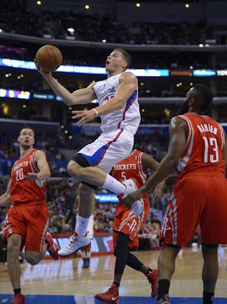 Los Angeles Clippers forward Blake Griffin, second from left, goes up for a shot as Houston Rockets forward Donatas Motiejunas, left, of Poland, forward Jordan Hamilton, second from right, and guard James Harden defend during the first half of an NBA basketball game, Wednesday, Feb. 26, 2014, in Los Angeles. (AP Photo/Mark J. Terrill)