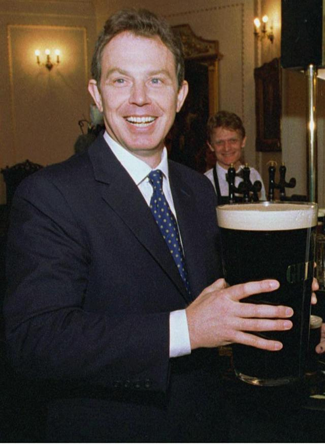 Then Labour party leader Tony Blair holds eight pints of Guinness in London when he was running for PM. (Reuters)