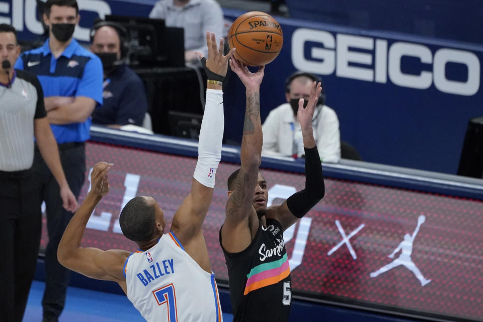 San Antonio Spurs guard Dejounte Murray (5) shoots as Oklahoma City Thunder forward Darius Bazley (7) defends during the first half of an NBA basketball game Wednesday, Feb. 24, 2021, in Oklahoma City. (AP Photo/Sue Ogrocki)