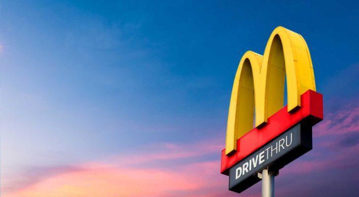 image of McDonald's (MCD) golden arches on a pole indicating a drive-through area with the sky at dusk in the background