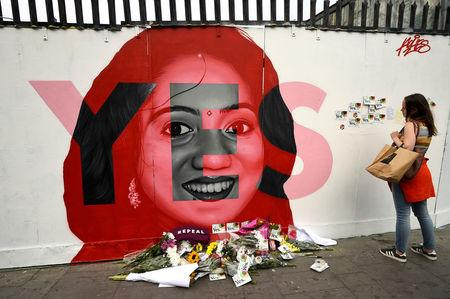 A woman looks at a new mural of Savita Halappanavar with flowers placed beneath it put up on the day of the Abortion Referendum on liberalising abortion laws in Dublin