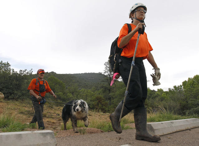<p>Members of the Tonto Rim Search and Rescue team exit a section of forest after searching along the banks of the East Verde River for victims of a flash flood, Sunday, July 16, 2017, in Payson, Ariz. (AP Photo/Ralph Freso) </p>