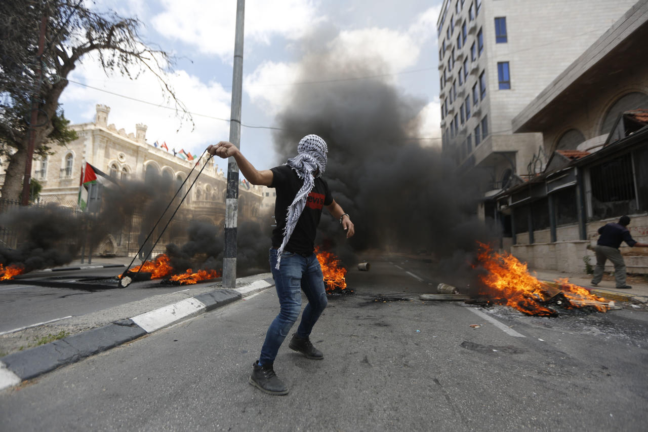 <p>Palestinians sling stonesin the West Bank city of Bethlehem during clashes with Israeli troops during a protest against the U.S. decision to relocate its embassy to Jerusalem, May 14, 2018. (Photo: Majdi Mohammed/AP) </p>