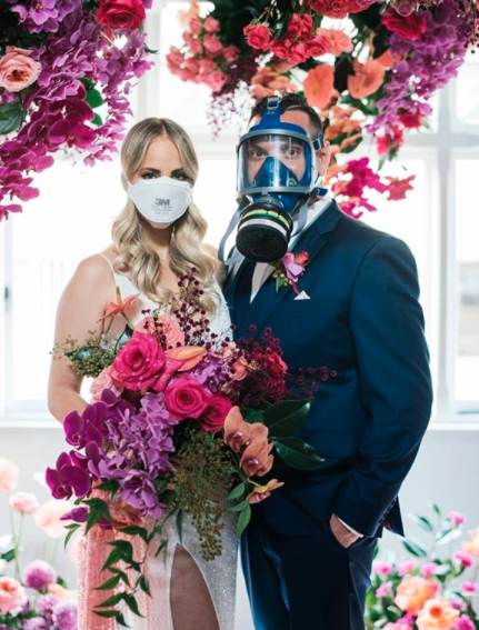 Bride holding colourful flowers wearing a face mask