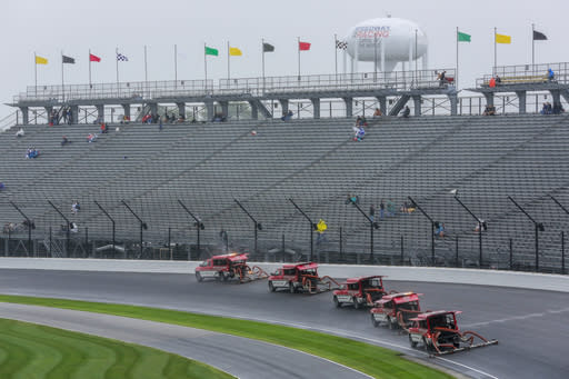 Trucks try to dry the track during a rain delay before a NASCAR Brickyard 400 auto race at Indianapolis Motor Speedway in Indianapolis, Sunday, Sept. 9, 2018. The race was postponed until Monday, Sept. 10. (AP Photo/R Brent Smith)