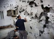 Israeli men inspect the damage caused to a house by a rocket launched by Palestinian militants from the Gaza Strip in the southern Israeli town of Ofakim. On Sunday, about 125 rockets hit Israel, while scores more were intercepted in mid-flight by the Iron Dome defence system, the army said