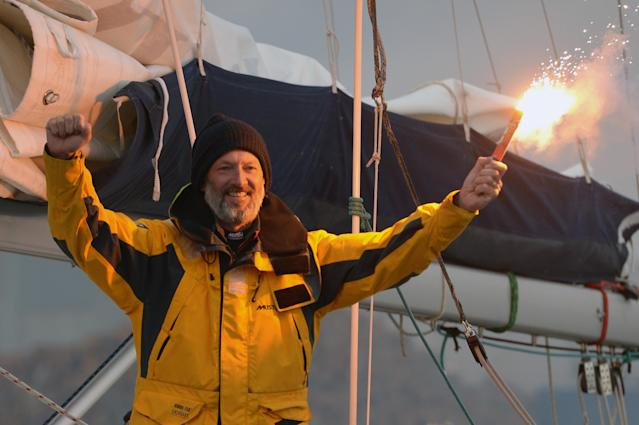 TROON, SCOTLAND - MAY 08: Gerry Hughes lights a flare on his yacht Quest III at Troon Marina on May 8,2013 in Troon,Scotland. The 55 year old sailor from Glasgow is the first deaf person to sail single handed around the world, he was greeted back in Scotland by a crowd of around 300 people. (Photo by Jeff J Mitchell/Getty Images)