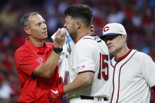 Cincinnati Reds' Nick Senzel (15) winces after taking a foul tip ball to the face during the fifth inning of the team's baseball game against the Texas Rangers, Saturday, June 15, 2019, in Cincinnati. (AP Photo/John Minchillo)