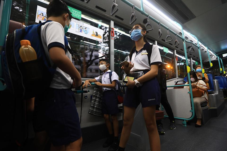 SINGAPORE - JUNE 08:  Students wearing protective masks commute to school by bus on June 8, 2020 in Singapore. The authority decided to remove all safe distancing stickers and markers from trains and buses as they deemed it is too challenging for commuters to keep their social distance. From June 2, Singapore embarked on phase one of a three phase approach against the coronavirus (COVID-19) pandemic as it began to ease the partial lockdown measures by allowing the safe re-opening of economic activities which do not pose high risk of transmission. This include the resumption of selected health services, re-opening of schools with school children attending schools on rotational basis, manufacturing and production facilities, construction sites that adhere to safety measures, finance and information services that do not require interactions and places of worship, amongst others. Retail outlets, social and entertainment activities will remain closed and dining in at food and beverage outlets will still be disallowed. The government will further ease restriction by the middle of June if the infection rate within the community remains low over the next two weeks.  (Photo by Suhaimi Abdullah/Getty Images)