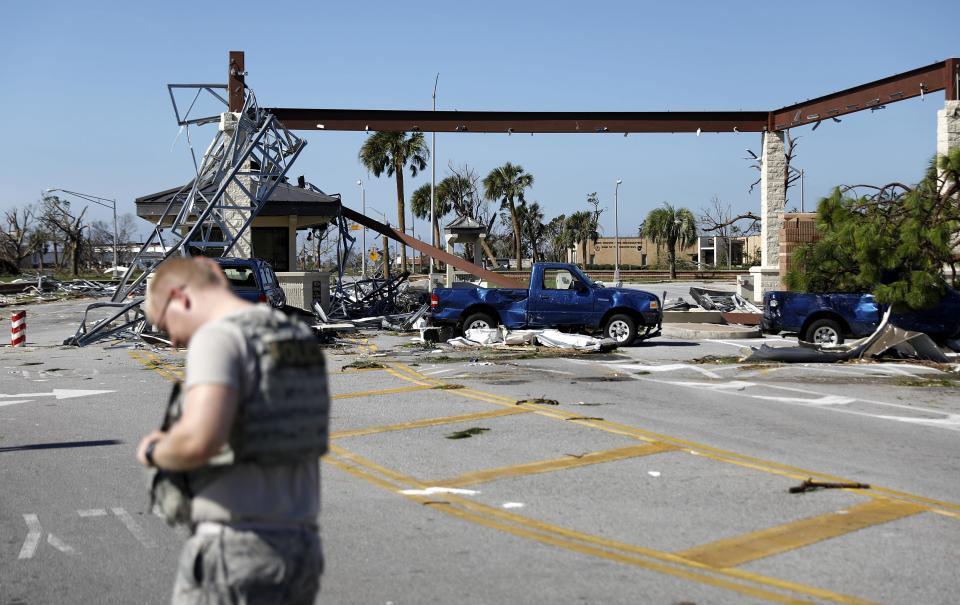 A soldier stands guard at the damaged entrance to Tyndall Air Force Base in Panama City, Fla., Thursday, Oct. 11, 2018, in the aftermath of hurricane Michael. The devastation inflicted by Hurricane Michael came into focus Thursday with rows upon rows of homes found smashed to pieces, and rescue crews began making their way into the stricken areas in hopes of accounting for hundreds of people who may have stayed behind. (AP Photo/David Goldman)