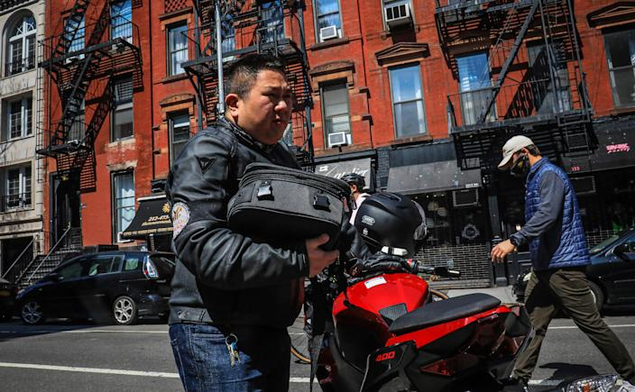 Eddie Song, a Korean American entrepreneur, prepares to ride his motorcycle wearing a jacket over extra body padding while equipped with video cameras Sunday April 19, 2020, in East Village neighborhood of New York. The coronavirus first seen in China is now ravaging the United States, and Asian Americans are continuing to wrestle with a second epidemic: hate. Hundreds of attacks on Asian people have been reported, with few signs of decline.