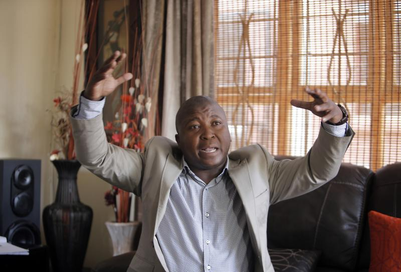 Thamsanqa Jantjie gesticulates at his home during an interview with the Associated Press in Johannesburg, South Africa,Thursday, Dec. 12, 2013. Jantjie, the man accused of faking sign interpretation next to world leaders at Nelson Mandela's memorial, told a local newspaper that he was hallucinating and hearing voices. (AP Photo/Tsvangirayi Mukwazhi)