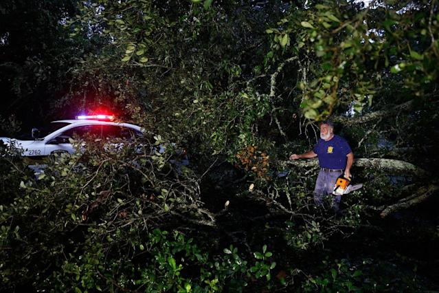 <p>Andy Jones clears away limbs from a tree blocking a road after it fell over from Hurricane Matthew on St. Simons Island, Ga., Saturday, Oct. 8, 2016. (Photo: David Goldman/AP) </p>