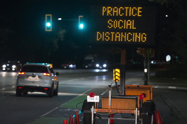 """In this Wednesday, March 18, 2020 file photo, a sign reminding people about """"social distancing"""" in the midst of the COVID-19 coronavirus outbreak stands next to a roadway in North Vancouver, British Columbia, Canada. Many see """"social distancing"""" to be the greatest pandemic-era addition the vernacular yet — easily understood phrasing that's helped communicate to millions that they need to keep a safe berth to avoid spreading the virus. (Jonathan Hayward/The Canadian Press via AP)"""