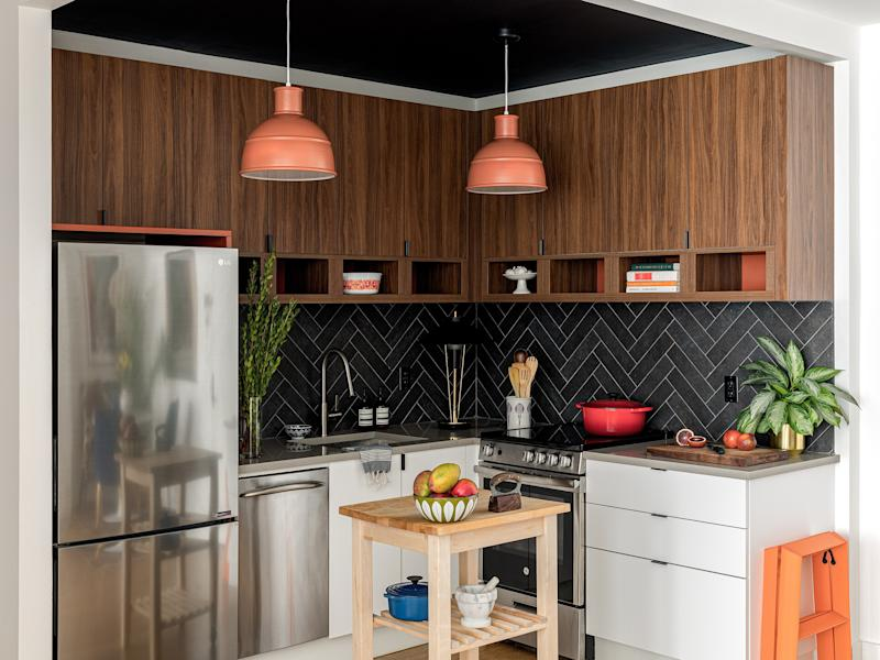 "The addition of a small butcher block island makes the fully updated kitchen even more functional. ""We loved the look of the dark herringbone tile in the kitchen, and the walnut cabinets add some much needed warmth,"" Sean says."