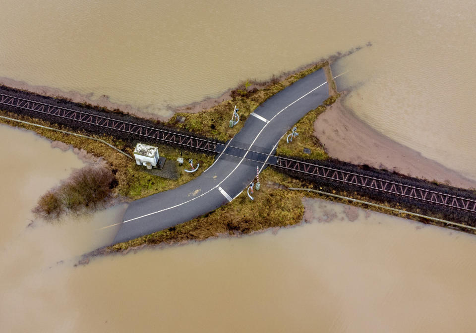 A railroad crossing is surrounded by floodwaters from rain and melting snow in Nidderau near Frankfurt, Germany, Wednesday, Feb. 3, 2021. (AP Photo/Michael Probst)