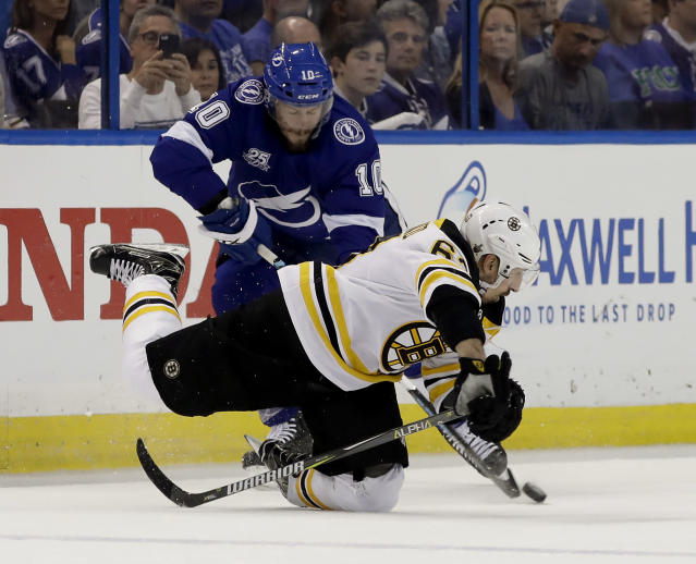 Boston Bruins left wing Brad Marchand, lower right, falls after getting tangle up with Tampa Bay Lightning center J.T. Miller (10) during the first period of Game 2 of an NHL second-round hockey playoff series Monday, April 30, 2018, in Tampa, Fla. (AP Photo/Chris O'Meara)