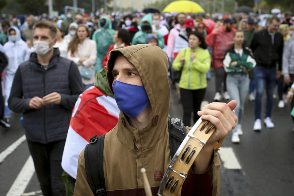 A demonstrator wearing a face mask to protect against coronavirus attends an opposition rally to protest the official presidential election results in Minsk, Belarus, Sunday, Sept. 27, 2020.Hundreds of thousands of Belarusians have been protesting daily since the Aug. 9 presidential election. (AP Photo/TUT.by)