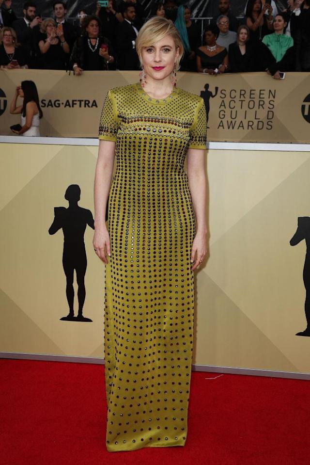 <p>Gerwig went for a yellow dress decorated with copper and silver grommets. (Photo: Getty Images) </p>