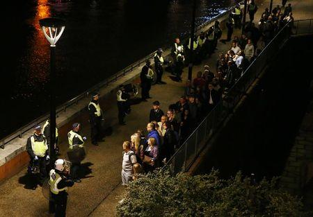 Police officers stand with people evacuated from the area after an incident near London Bridge in London, Britain June 4, 2017. REUTERS/Neil Hall