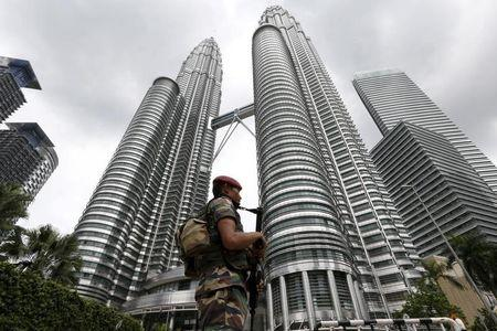 A Malaysian soldier patrols in front of the Petronas towers at the venue of the 27th ASEAN summit in Kuala Lumpur