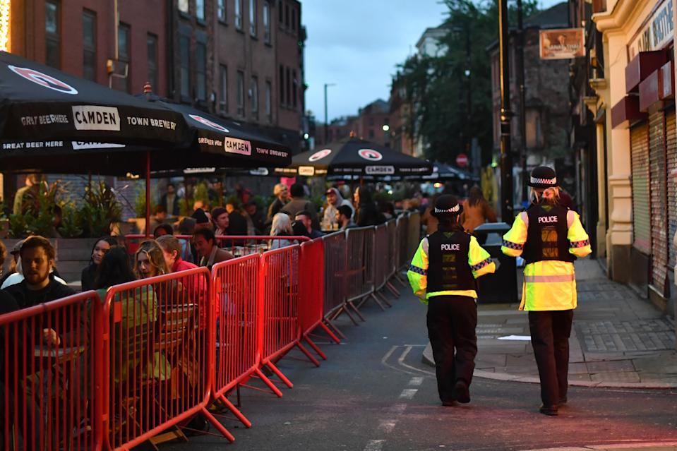 MANCHESTER, ENGLAND - JULY 04: Police officers patrol as bars on Thomas Street in the Northern Quarter set out tables for customers on the closed road on July 04, 2020 in Manchester, England. The UK Government announced that Pubs, Hotels and Restaurants can open from Saturday, July 4th providing they follow guidelines on social distancing and sanitising.  (Photo by Anthony Devlin/Getty Images)