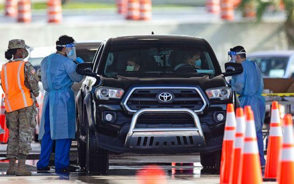 PHOTO: A National Guard troop directs cars as people are tested by healthcare workers at the COVID-19 drive-thru testing center at Hard Rock Stadium, in Miami Gardens, Fla., as the coronavirus pandemic continues, July 19, 2020. (David Santiago/AP)