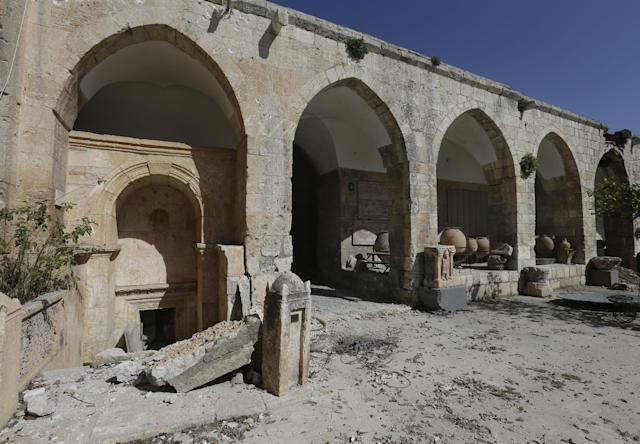 In this photo taken Tuesday, Feb. 26, 2013, damage caused by shelling at a 17th-century caravanserai, which presently serves as a headquarters for the Free Syrian Army, in Maaret al-Numan, Idlib province, Syria. Across northern Syria, rebels, soldiers and civilians are making use of the country's wealth of ancient and medieval remains for protection. The structures are built of thick stone that has already withstood the ravages of centuries. They are often located in strategic spots overlooking towns and roads. (AP Photo/Hussein Malla)