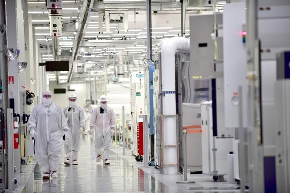 Intel employees wearing clean-room suits at a manufacturing plant.