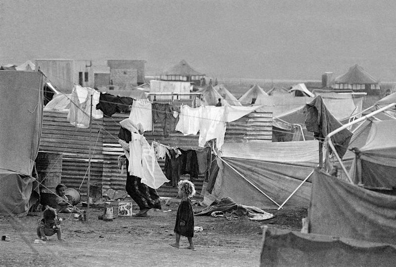 "FILE - In this Oct. 18, 1969 file photo, children play amidst lines of laundry drying out at Baqaa Camp on the Jordan desert, a home for Palestinian refugees. In peace talks to be held in Washington beginning Monday, July 29, 2013, Palestinians demand that Israel recognize the ""right of return"" for Palestinian refugees, defined as more than 700,000 people who fled or were driven from their homes in what is now Israel, as well as _ critically _ their millions of descendants.(AP Photo, File)"