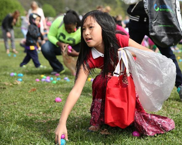 Michelle Liu, 8, scrambles to get eggs during the Easter egg hunt at Camp Jordan Park in East Ridge, Tenn., on Saturday, April 5, 2014. The event was put on by Venue Church. (AP Photo/Chattanooga Times, Erin O. Smith)