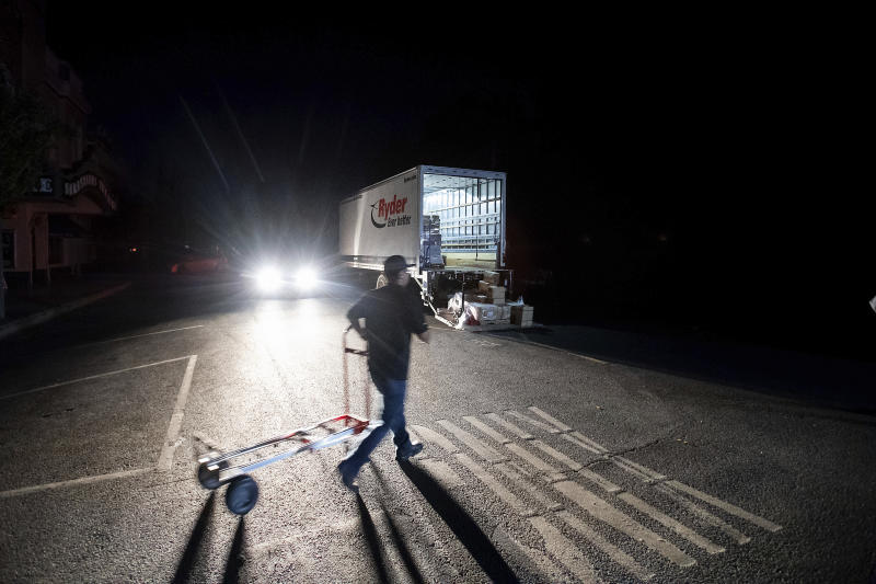 Armando Espinoza delivers paper products to a cafe in downtown Sonoma, Calif., where power is turned off, on Wednesday, Oct. 9, 2019. Pacific Gas & Electric has cut power to more than half a million customers in Northern California hoping to prevent wildfires during dry, windy weather throughout the region. (AP Photo/Noah Berger)