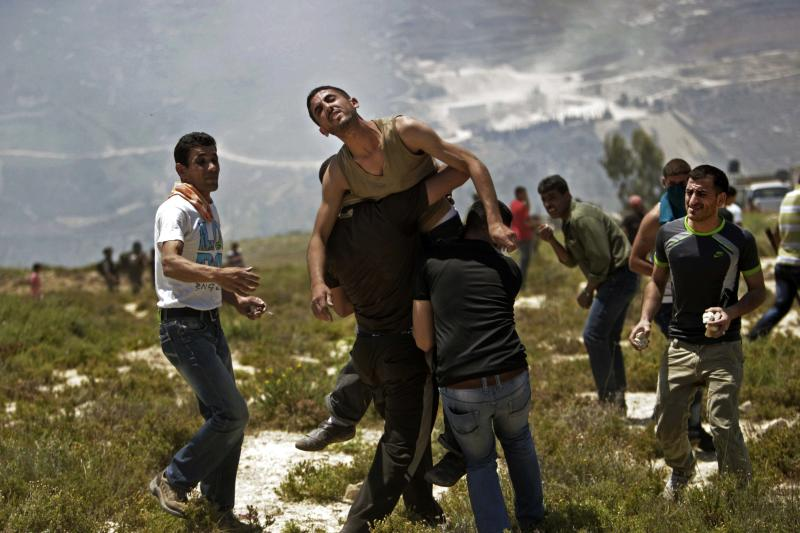 Palestinians help a wounded man during clashes with Jewish settlers near the Jewish settlement of Yitzhar, near Nablus, Tuesday, April 30, 2013. In the West Bank, a Palestinian man fatally stabbed an Israeli waiting at a bus stop and fired on police before he was detained by Israeli security forces, officials said. (AP Photo/Nasser Ishtayeh)
