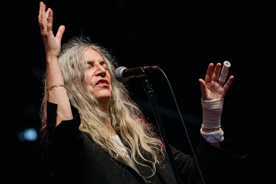Patti Smith performing behind a microphone with long grey hair