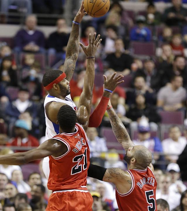 Detroit Pistons forward Josh Smith (6) shoots over the defense of Chicago Bulls guard Jimmy Butler (21) and forward Carlos Boozer (5) during the first half of an NBA basketball game in Auburn Hills, Mich., Wednesday, March 5, 2014. (AP Photo/Carlos Osorio)