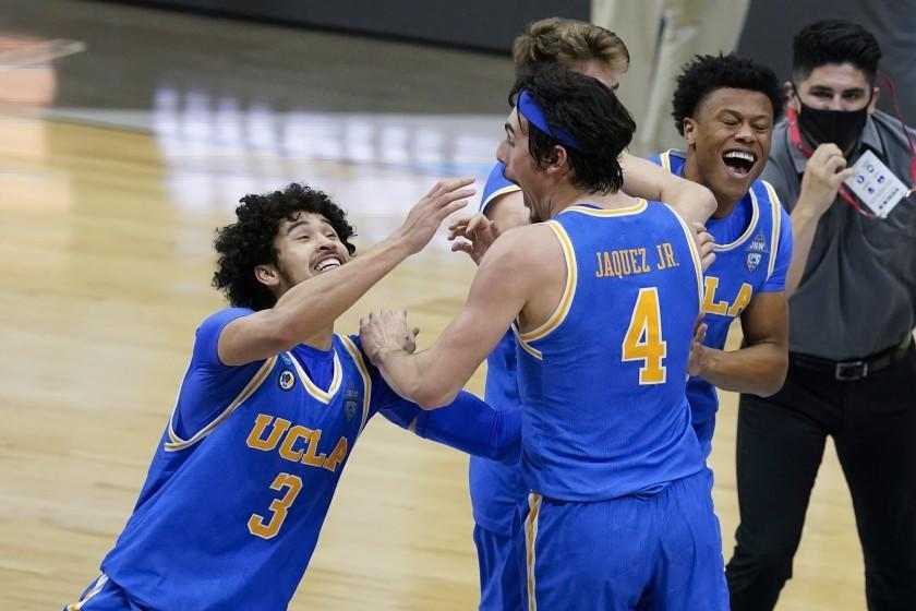 UCLA guard Johnny Juzang (3) and guard Jaime Jaquez Jr. (4) celebrate after an Elite 8 game against Michigan in the NCAA men's college basketball tournament at Lucas Oil Stadium, Wednesday, March 31, 2021, in Indianapolis. UCLA won 51-49. (AP Photo/Darron Cummings)