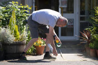 David Waugh, head teacher at Poynton High School and Education Trust Leader sprays safe distance markers on the ground as measures are taken to prevent the transmission of coronavirus before the possible reopening of Lostock Hall Primary school in Poynton near Manchester, England, Wednesday May 20, 2020. (AP Photo/Jon Super)
