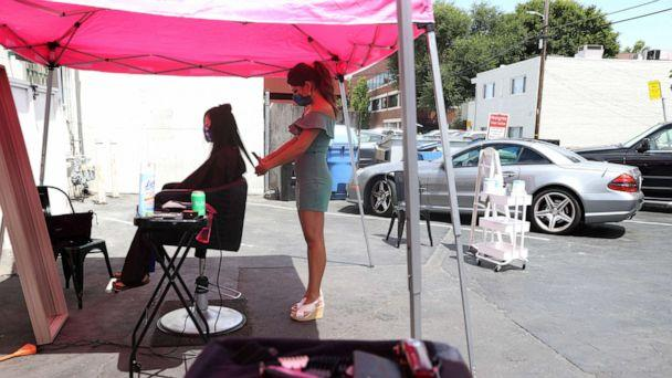PHOTO: Insignia Hair Salon stylist Regina Muslimova gives a haircut in the parking lot behind the salon, July 21, 2020, in Walnut Creek, California. (Justin Sullivan/Getty Images)