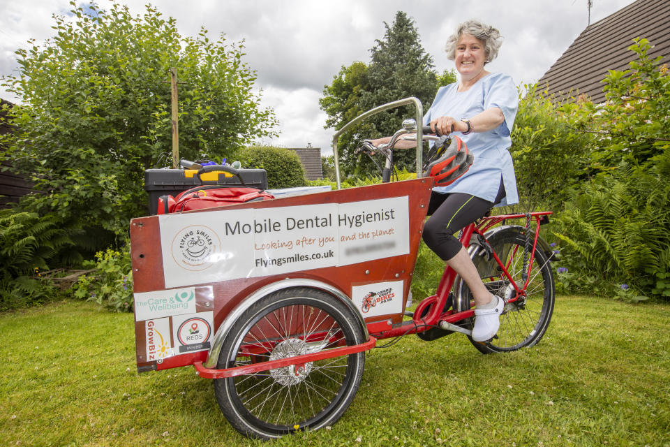 Perry cycles between houses with her equipment on a cargo bike. (SWNS)