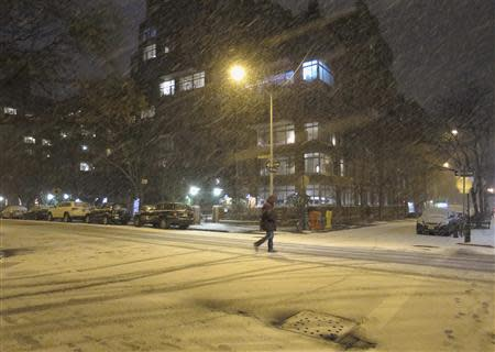 A man walks through the West Village neighbourhood as snow begins to fall in New York
